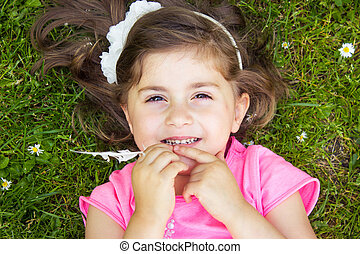 Little girl laying in the grass