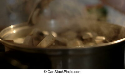 The women's hand is stirring soup with mushrooms. Soup is...