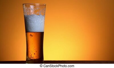 Beer poured in glass on yellow background.