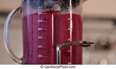 A woman makes a fruit smoothie in a blender