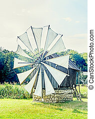 Windmill close up, green forest, wild vegetation, blue clouds sky