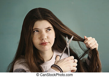 teen girl tired with her hair cut it with scissors