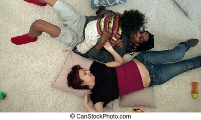 Happy mixed family with child lying on the floor - Top view...