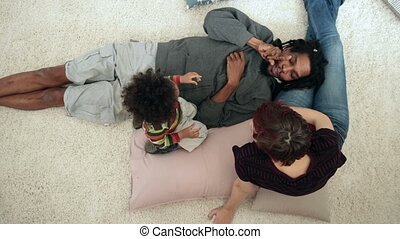 Diverse family with toddler boy lounging at home -...