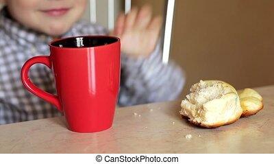 Boy having a piece of bun