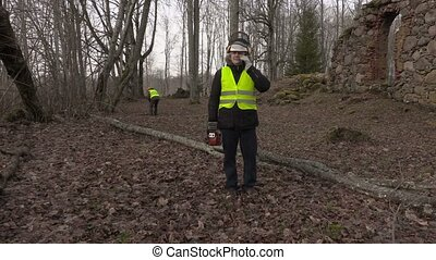 Worker with chainsaw and phone near fallen tree