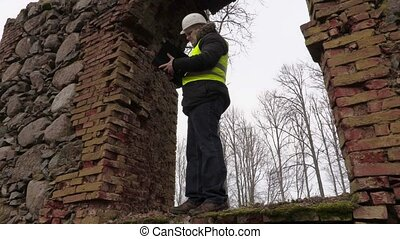 Building inspector checking old brick wall
