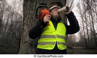 Worker with chainsaw on shoulder near tree drinking coffee