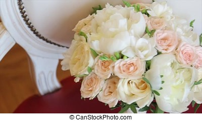 Wedding bouquet of roses. Bride's bouquet on wedding day. Bouquet of different flowers. Bouquet of beautiful pink and white or red roses on the dressing stool. Roses