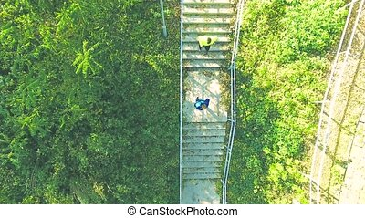 Two athletes running on stairs in sunny autumn nature.