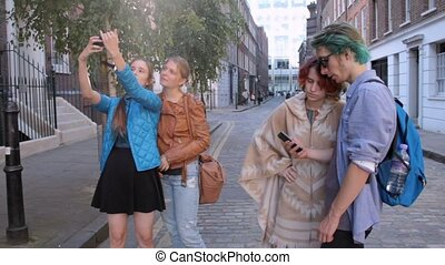 Three happy hipster young women and one guy are walking the streets of London. Do selfies, laughing and joking. On summer vacation.