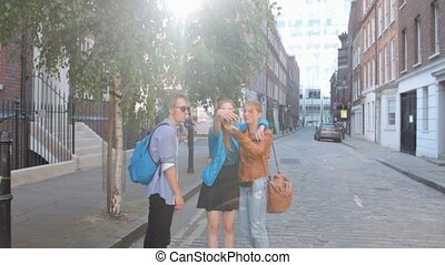 Four friends are walking the streets of London. Do selfies, laughing and joking. On summer vacation.