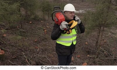Worker with chainsaw on shoulder talking on phone on  steep forest slope