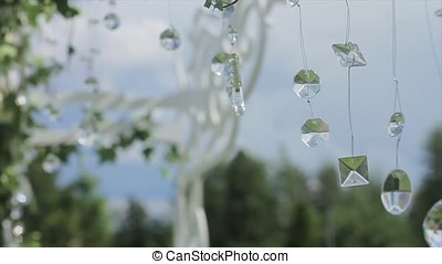 Part of the festive decor, floral arrangement. Detail of a wedding arch. Wedding decoration ceremony Chandelier in the arch of flowers . Wedding decoration. Arch. Cage. Wedding setup on the beach. wedding arch decorated with flowers. Diamonds