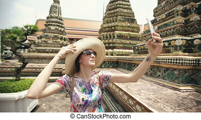 Young woman tourist taking selfie with smartphone at temple sightseeing in Bagnkok Thailand during traveling