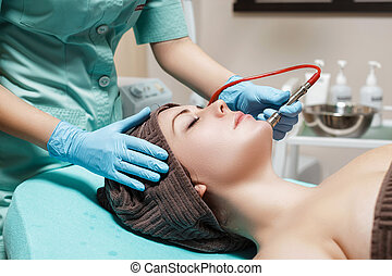 Beautician makes mechanical cleaning of face. Procedure of...