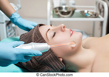 Face Beauty Treatment. Beautician makes Facial Darsonval...
