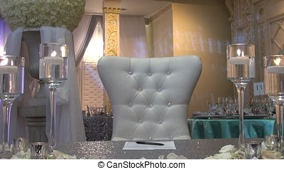 Wedding table at a wedding feast decorated with bridal bouquet. Banquet hall. festive table for the bride and groom decorated with cloth and flowers. Table set for bride and groom. Wedding