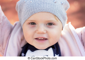 Portrait of a beautiful toddler smiling; baby girl with winter hat enjoying autumn day in the park