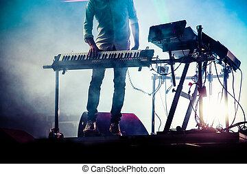 disc jokey mixing on stage over illuminated smoke background...