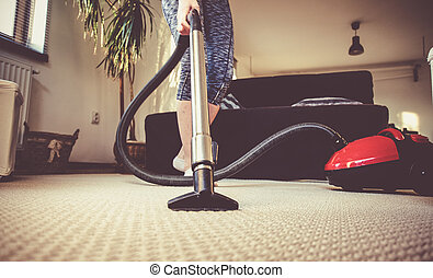 woman cleaning carpet with a vacuum cleaner in room - focus...