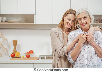 Cheerful woman embracing her senior parent in kitchen - We...