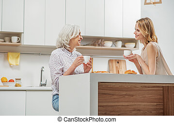 Lovely adult daughter talking with mom at home - Friendly...