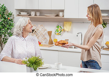 Cute daughter treating her mom with breakfast - Help...