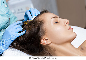 Needle mesotherapy. Cosmetic been injected in woman's head....