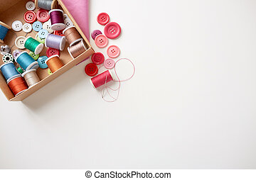 box with thread spools and sewing buttons on table -...