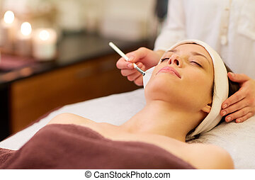 beautician applying facial mask to woman at spa