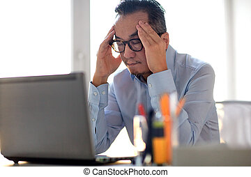 businessman in eyeglasses with laptop at office - business,...