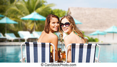 happy young women with drinks sunbathing on beach - summer...