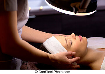 beautician doing face massage to woman at spa