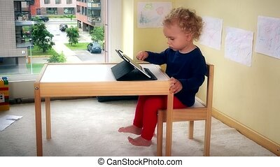 Lovely kid playing with tablet pc sitting on small chair near table.