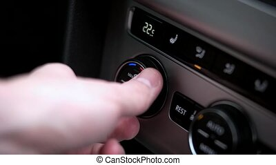 Man sets the air condition temperature in the car