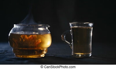 Chinese green tea Bud blooms in a glass teapot. A Cup of tea