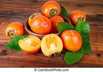 Kaki fruit ripe persimons on old wooden background