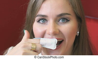 Young woman brushes tooth using nylon fabric