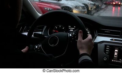 Man drives a car in the city inside view