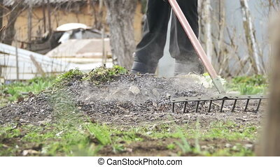 Woman is Cleaning the Weeds in the Garden with Rake Tool. Slow Motion