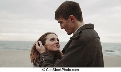 Young couple looking at the sea, walking the beach, coat and...