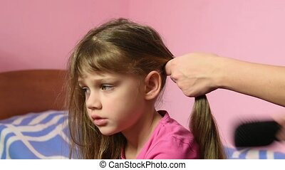 Mother combing her long hair girls and braid them into a...