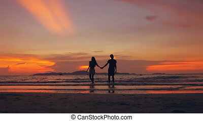 Slow motion silhouette of happy loving couple walk at beach on sunset in ocean shore
