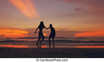 Slow motion silhouette of happy loving couple meet and play at the beach on sunset in ocean shore