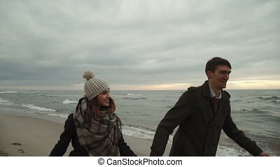 Young couple Run on the beach at the sea, walking the beach,...
