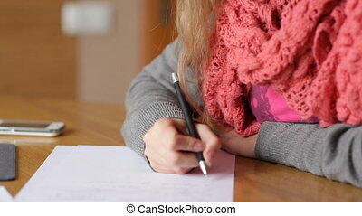 Young business woman writing pen on sheet of paper at office