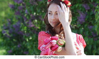 Beautiful young woman in a spring park with a wreath of flowers