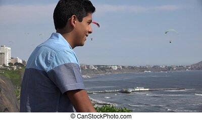 Teen Boy Watching Parasailing