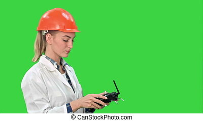 Female construction worker operating a crane using remote control on a Green Screen, Chroma Key.